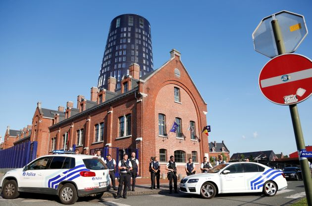Belgian police officers stand guard outside the main police station after a machete-wielding man injured...