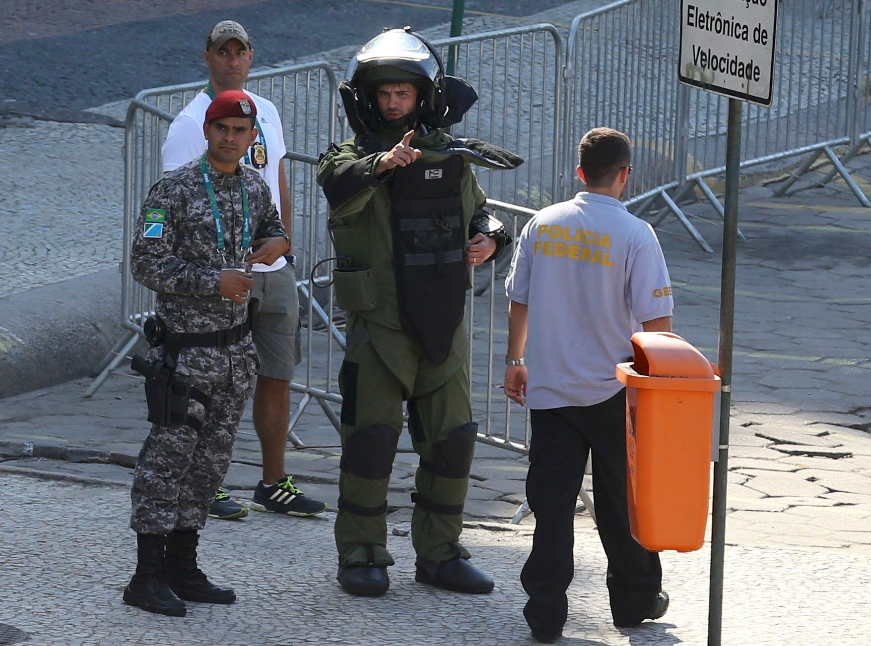 An agent of the bomb squad in protective clothing stands in the area near the finishing line of the men's...