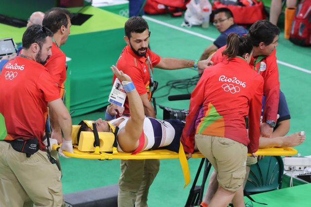 Said gestures to the crowd as he is stretchered
