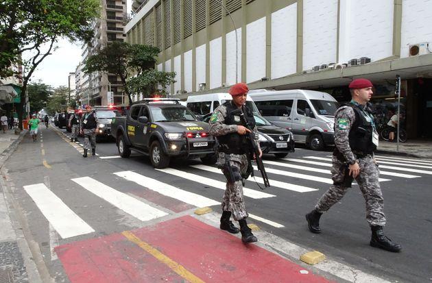 Security personnel walk along Copacabana