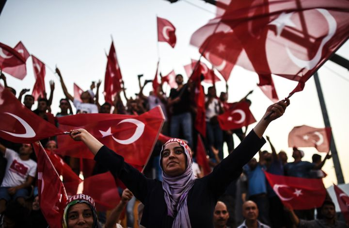 Demonstrators wave Turkish national flags as they stand in front of giant screens on August 7, 2016.