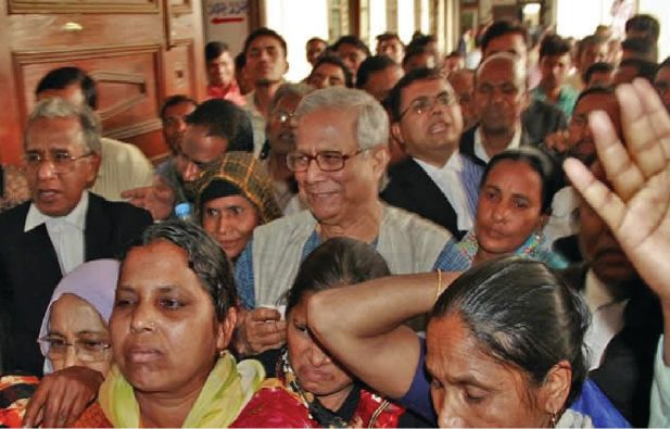 Yunus is flanked by lawyers and Grameen borrowers on the premises of the High Court on Thursday after he went to the court to