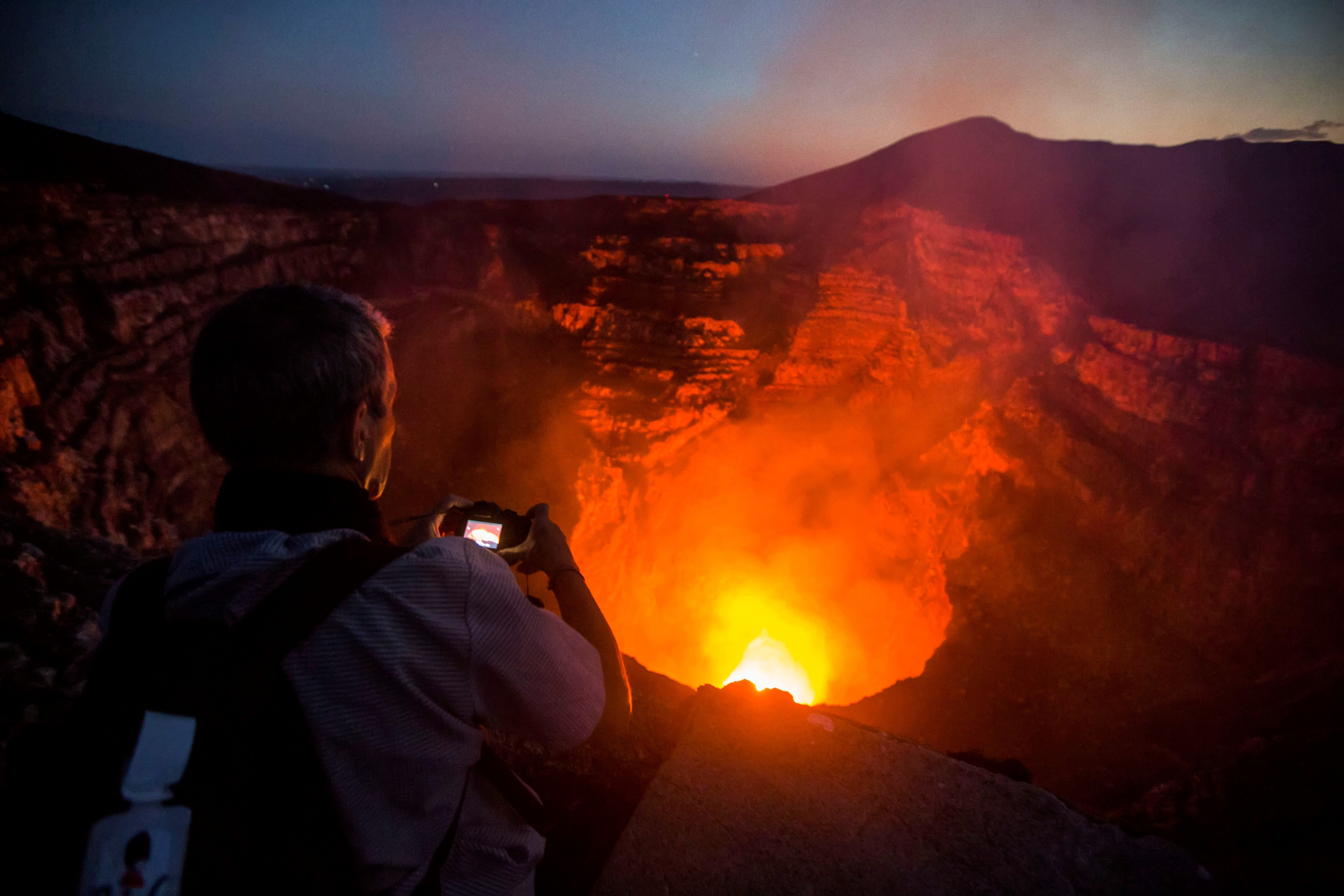A tourist takes pictures of a lava lake inside the crater of the Masaya Volcano in Masaya, some 30km from Managua on May 19, 2016. Hundreds of tourists arrive daily to observe the lava flow which formed six months ago near the surface of the crater of the small Masaya volcano, one of the most active in Nicaragua.  / AFP / INTI OCON / TO GO WITH AFP STORY BY BLANCA MOREL        (Photo credit should read INTI OCON/AFP/Getty Images)