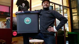 Stephan Martinez, owner of Le Petit Choiseuil bistrot, poses with a garbage container to collect food waste in Paris February 12, 2014. A group of Paris restaurants is turning food scraps into biogas and compost ahead of a new law that will force thousands of French food outlets to recycle their organic waste. Some 80 restaurants, caterers and hotels, signed up for a pilot project to collect their food waste, which is used to generate biogas and produce electricity and heat, as well as compost for farms around Paris. Martinez, who took the initiative for the project, said the collection anticipates the law but that participating restaurants are happy that someone collects their waste and puts it to good use.   REUTERS/Charles Platiau  (FRANCE - Tags: FOOD ENVIRONMENT SOCIETY ENERGY)