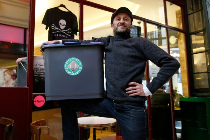 Stephan Martinez, owner of Le Petit Choiseuil bistrot, poses with a garbage container to collect food waste in Paris February