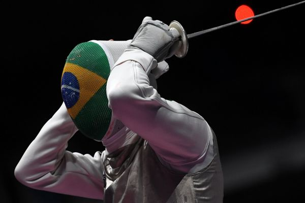 Brazil's Ghislain Perrier reacts as he competes against China's Ma Jianfei during their men's individual foil qualifying bout