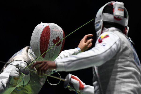 Canada's Maximilien Van Haaster (L) competes against Venezuela's Antonio J. Leal during their men's individual foil qualifyin