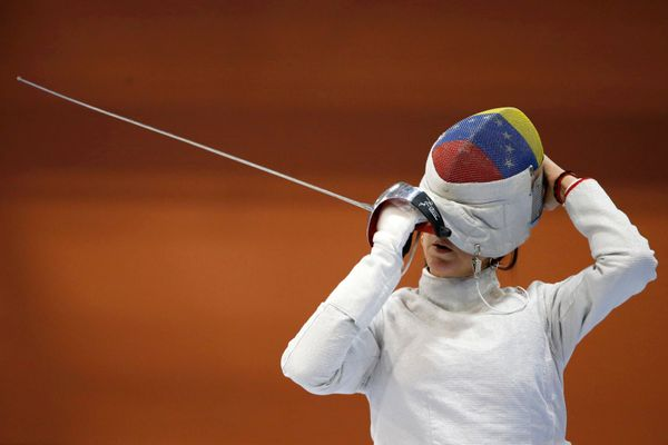 Venezuela's Alejandra Benitez adjusts her mask during practice.