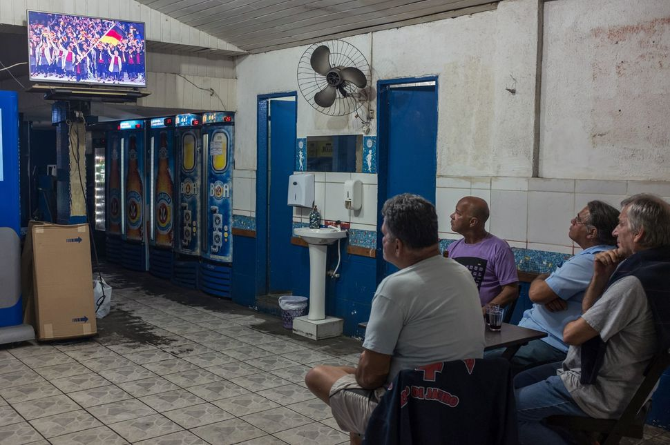 "People watch a television screen at a restaurant near the stadium.<br><br>""The Olympics only brought more social injustice, t"
