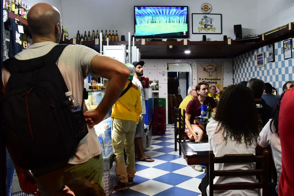 Locals watch on TV in a bar near the Maracana stadium in Rio de Janeiro.<br><br>&ldquo;Rio&rsquo;s residents will be working