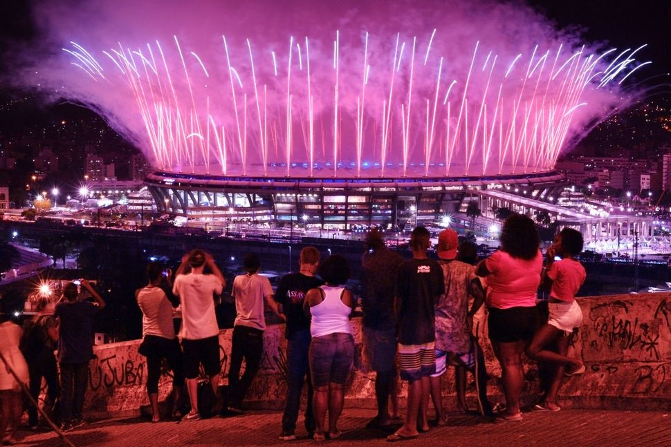 "People watch fireworks exploding over the Maracana stadium from the favela Mangueira.<br><br>""It's not the right moment,"" Adr"