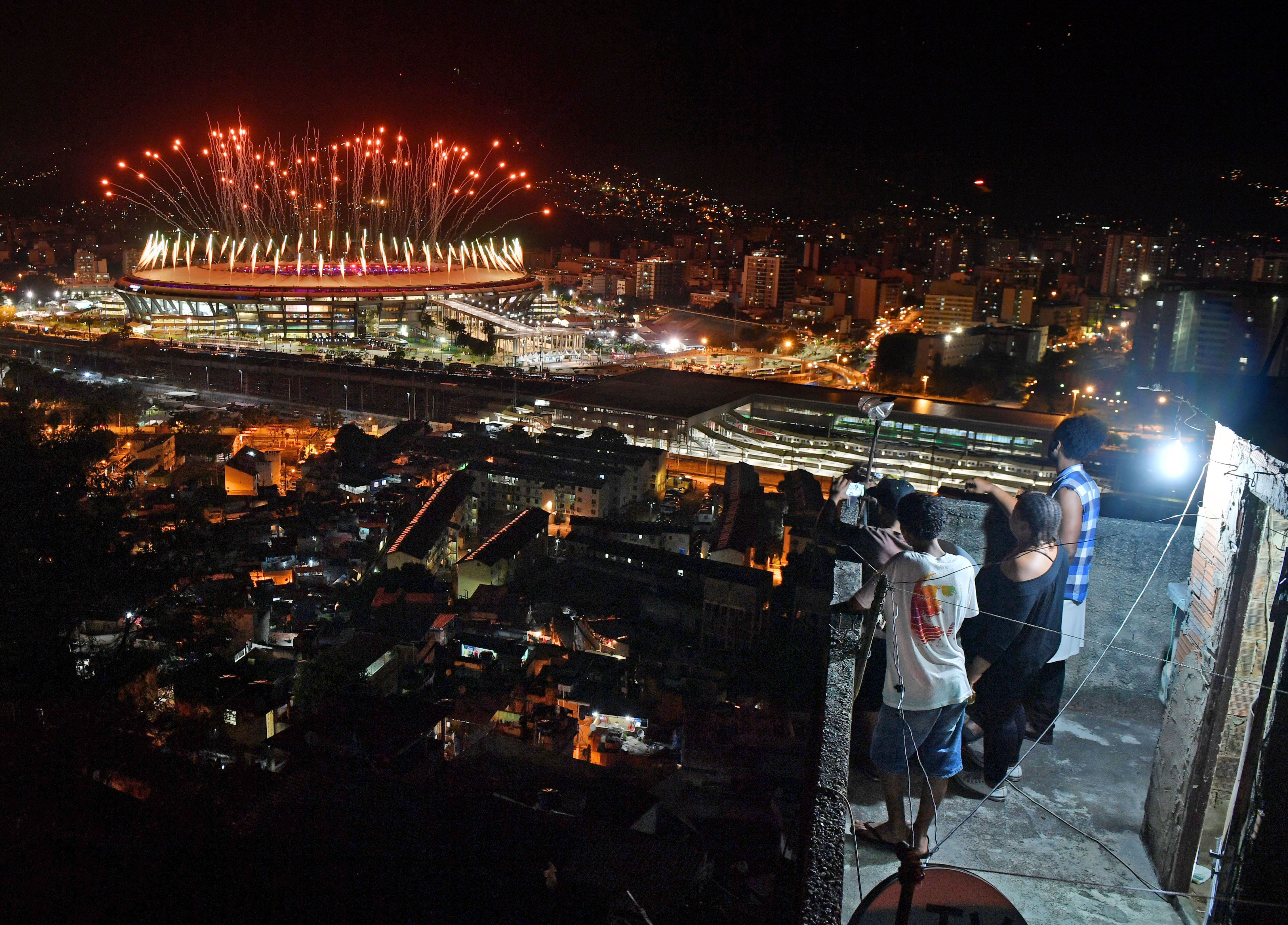 People watch fireworks exploding over the Maracana stadium from a terrace in the favela Mangueira during the opening ceremony