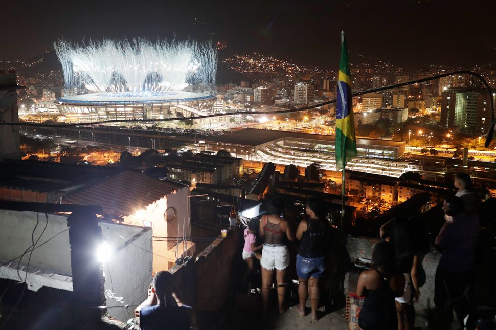 People watch fireworks explode over the Maracana from the roof of their home in the Mangueira favela.