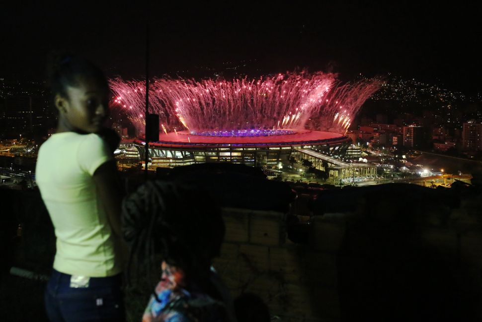People in the Mangueira favela watch fireworks.