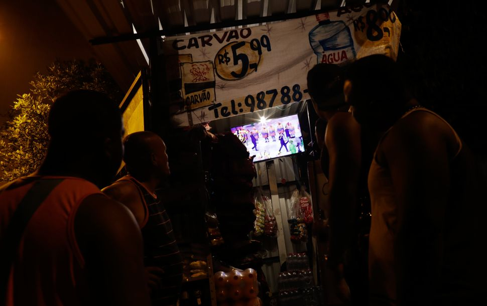 Residents of the Mangueira favela watch the opening ceremony on TV.