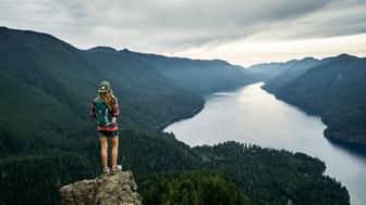 A woman hiking to a beautiful overlook above a lake.