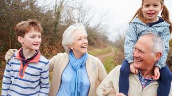 Grandparents With Grandchildren On Walk In Countryside Relaxing