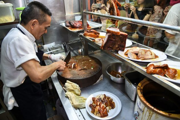 Chan Hon Meng chopping braised chicken at his Hong Kong Soya Sauce Chicken Rice and Noodle stall in