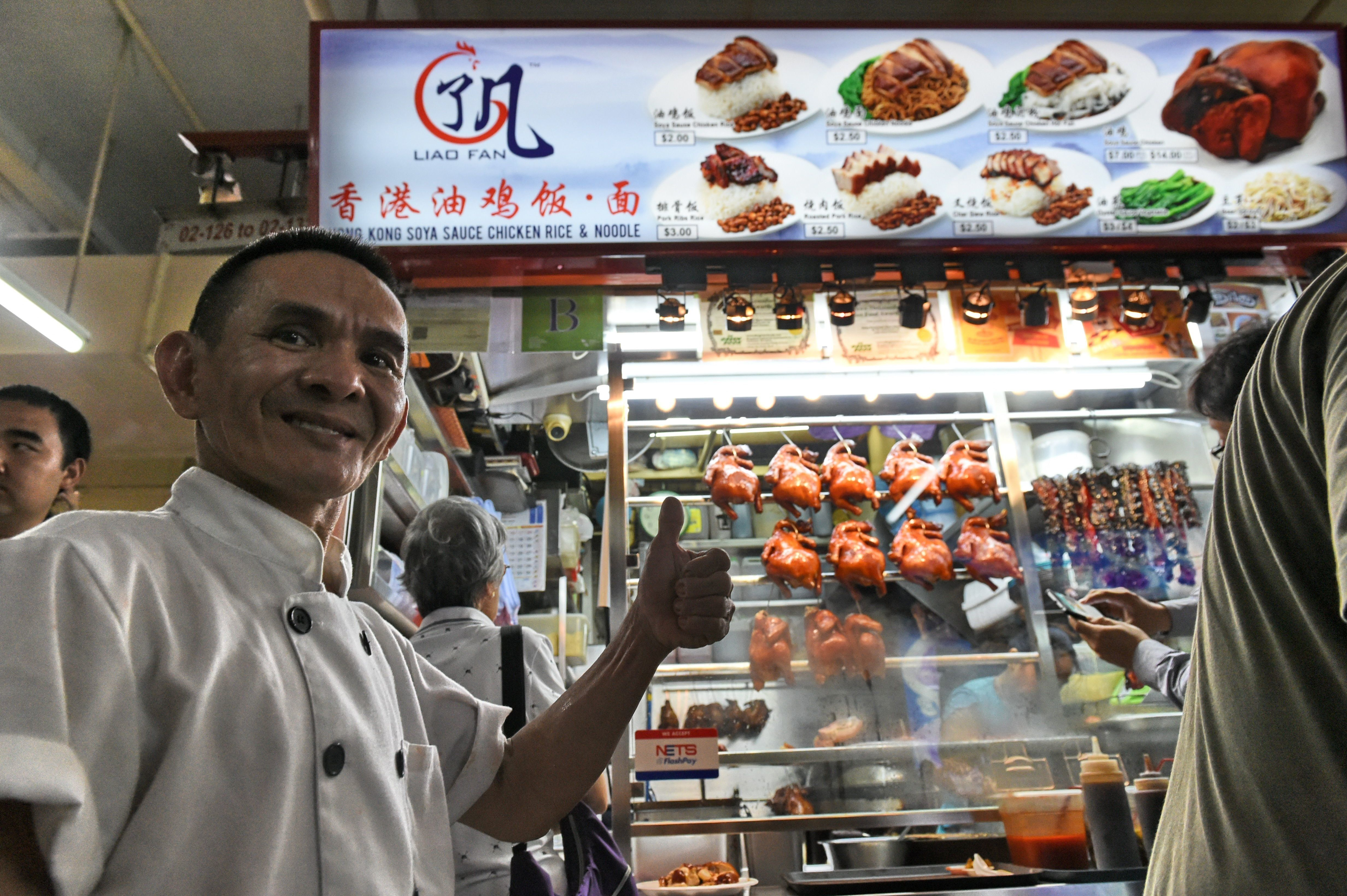 Singaporean chef Chan Hon Meng poses infront of his Hong Kong Soya Sauce Chicken Rice and Noodle stall in Singapore on July 2