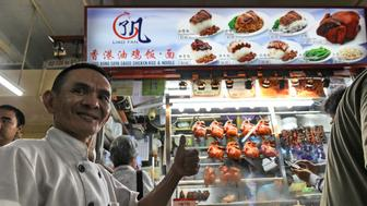 Singaporean chef Chan Hon Meng (front L) poses infront of his Hong Kong Soya Sauce Chicken Rice and Noodle stall in Singapore on July 22, 2016. Culinary bible Michelin on July 21 awarded one star each to two street food hawkers in Singapore, the first in the guide's history. Launching the inaugural restaurant and hotel guide to the Southeast Asian city-state, Michelin inspectors gave one star each to Hill Street Tai Hwa Pork Noodle and Hong Kong Soya Sauce Chicken Rice & Noodle. / AFP / ROSLAN RAHMAN        (Photo credit should read ROSLAN RAHMAN/AFP/Getty Images)