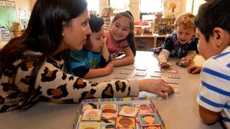 BOULDER, CO - MARCH 30:  Preschool teacher Fernanda Perez Chaves, {cq}, left, plays a memory game called 'I Never Forget a Face', with faces from all over the world, with students, from left to right, Elijah Hernandez, 4, Juliette Martinez, 5, in pink, Cohen Rose, right, during class at the Mapleton Early Childhood Center on March 30, 2016 in Boulder, Colorado. Preschools are looking at creative ways to incorporate gender and sexual diversity in their schools.  At the Mapleton Center teachers post pictures of children's families on walls, allow kids to bring framed photos of their family into class and read diverse books to them. The family photos not only make children feel more comfortable in class but also help to show their classmates the diversity in each family.  (Photo by Helen H. Richardson/The Denver Post via Getty Images)