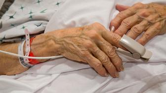 Senior woman with oxygen sensor on finger, close-up of hands