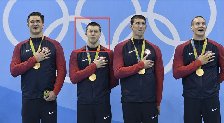 Nathan Adrian, Ryan Held, Michael Phelps and Caeleb Dressel listen to the U.S. national anthem as they stand on the podium of