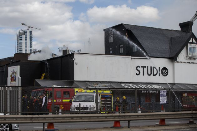 Fire brigade crew work to extinguish the fire at London nightclub 'Studio 338' on