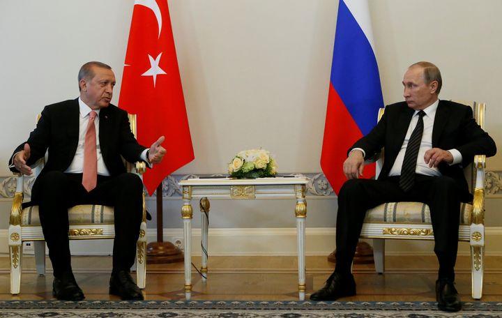 Turkish President Tayyip Erdogan speaks to Russian President Vladimir Putin (R) during their meeting in St. Petersburg, Russi