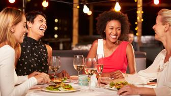 Group of female friends eating dinner at rooftop restaurant