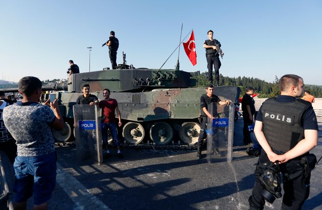 People pose with policemen after troops involved in the coup surrendered on the Bosphorus Bridge in Istanbul,...