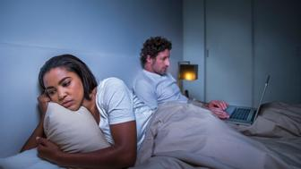 Sad woman reclining while man using laptop in bedroom