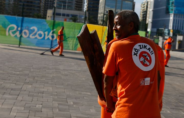 "A workers wears a sign which reads ""Shoo Zika!"" in Portuguese on his back in the Olympic park."