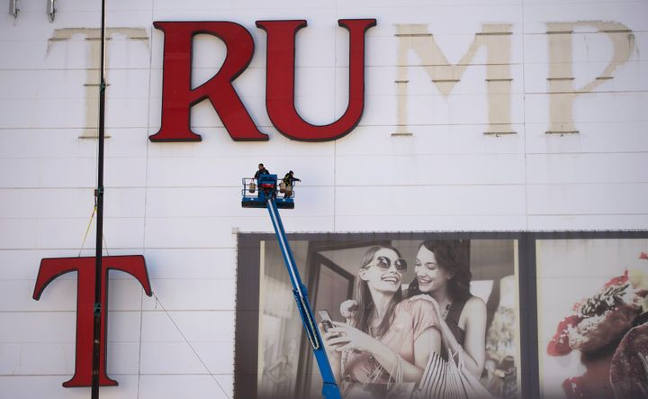 Workers remove letters from the Trump Plaza Casino signage in Atlantic City, New Jersey, in 2014.