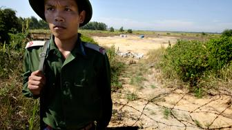 DA NANG, VIET NAM - JULY 1: A Viet Namese soldier guards the contaminated site at the edge of the Da Nang Airfield on July 1, 2009 in Da Nang, Central Viet Nam. During the Viet Nam War, the U.S. military stored more than four million of gallons of herbicides, including Agent Orange, at the military base that is now a domestic and military airbase. More than 30 years later there are still high levels of toxins in the soil, toxins that have seeped into a near by lake and have moved through the food chain into (Photo by Kuni Takahashi/Getty Images)