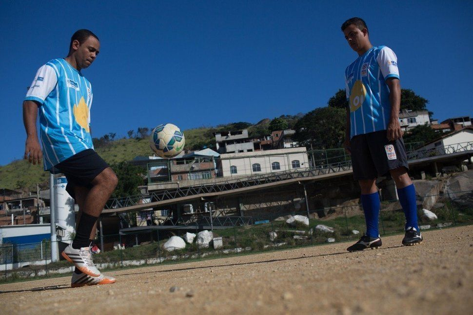 A policeman and a resident of the slum complex of Mangueirinha pass a soccer ball in Morro dos Macacos, a hillside area in no
