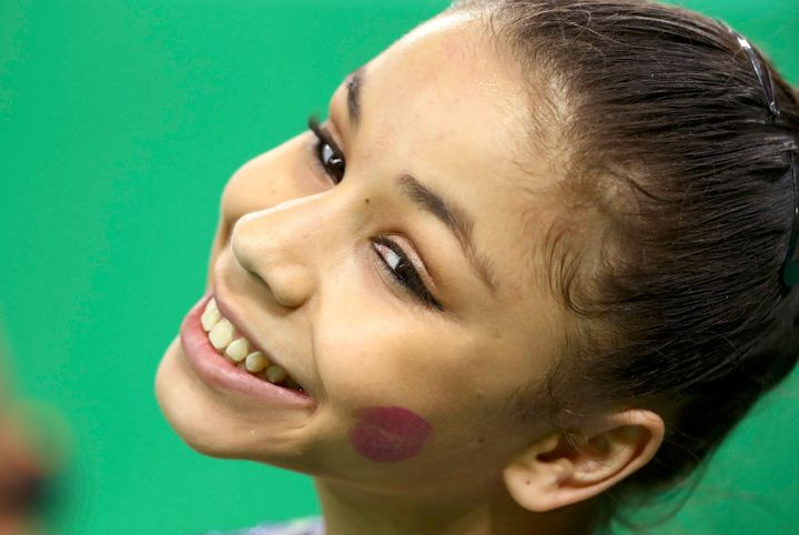 Flavia Saraiva of Brazil smiles with a lipstick kiss stain on her cheek during the women's qualifications.