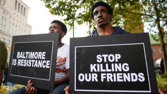 Jaz Jacobs (L) and Kevin Walloons gather to remember Freddie Gray and all victims of police violence during a rally outside city hall in Baltimore, Maryland, U.S., July 27, 2016.  REUTERS/Bryan Woolston