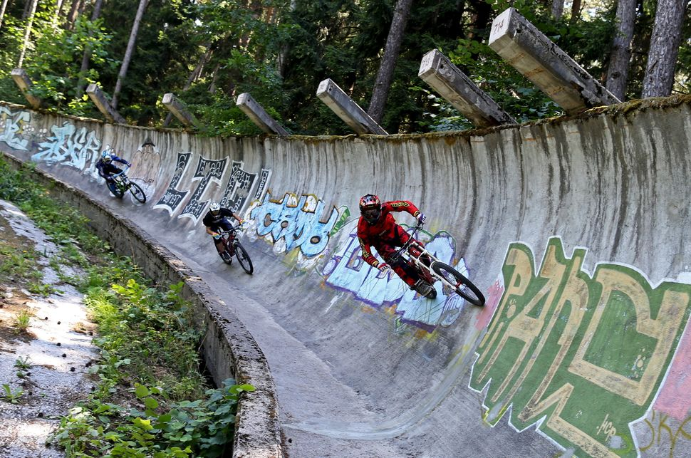 Downhill bikers Kemal Mulic (R-L), Tarik Hadzic and Kamer Kolar train on the disused bobsled track from the 1984 Sarajevo Win