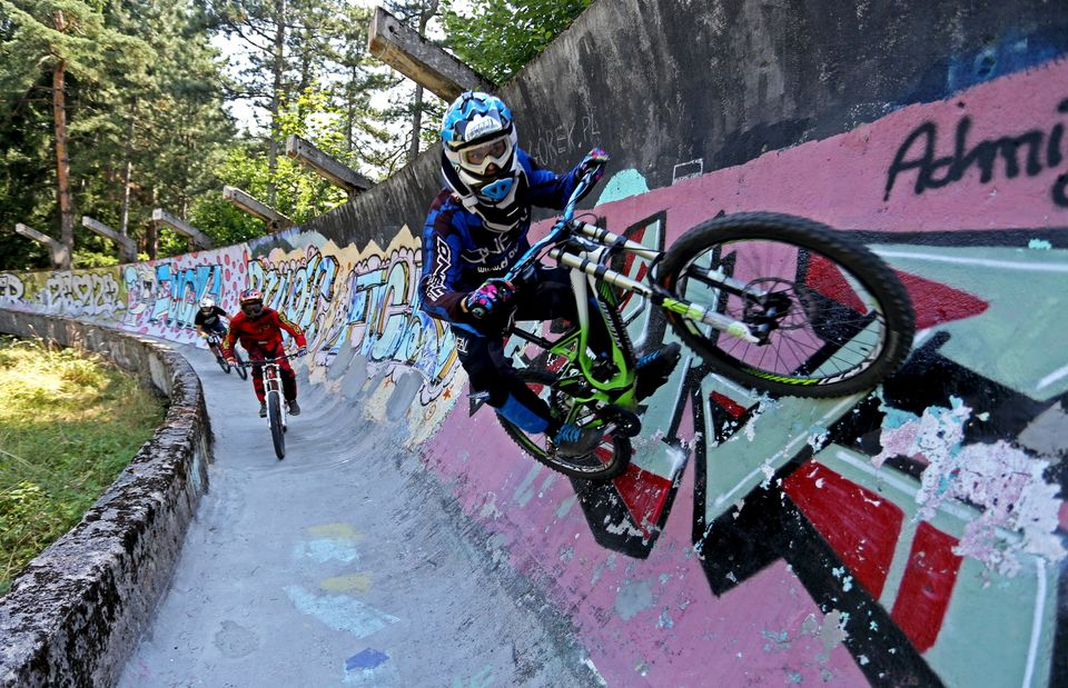 Downhill bikers Kemal Mulic (C), Tarik Hadzic (L) and Kamer Kolar train on the disused bobsled track from the 1984 Sarajevo W