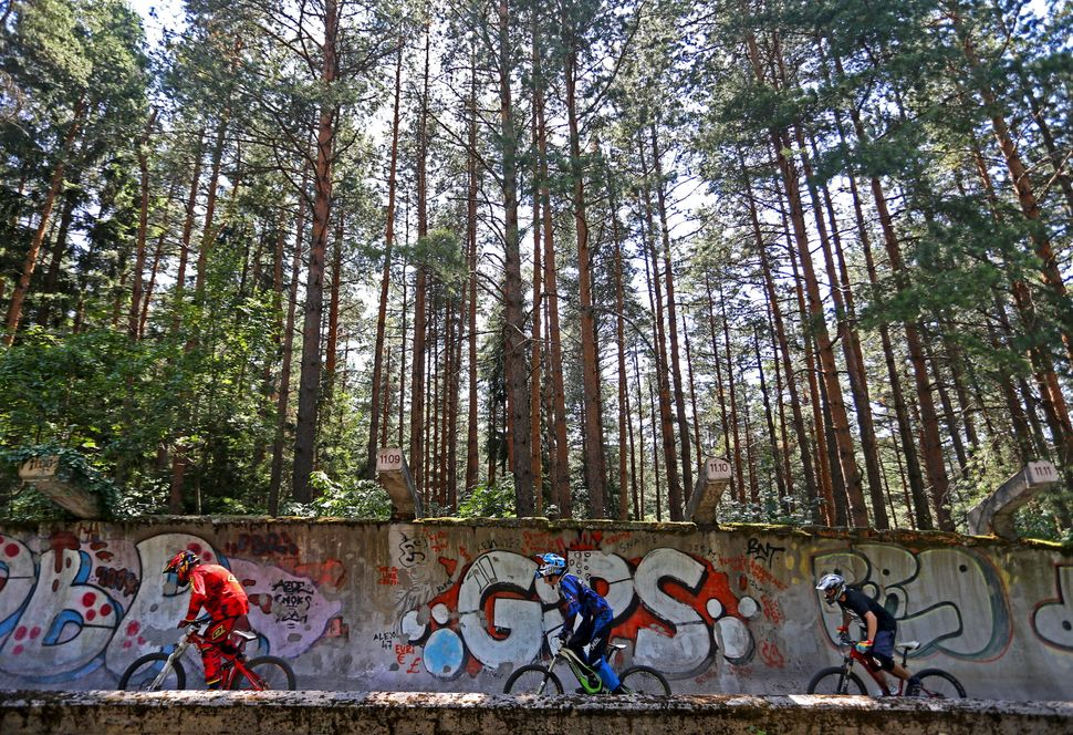 Downhill bikers Kemal Mulic (L-R), Kamer Kolar and Tarik Hadzic train on the disused bobsled track from the 1984 Sarajevo Win