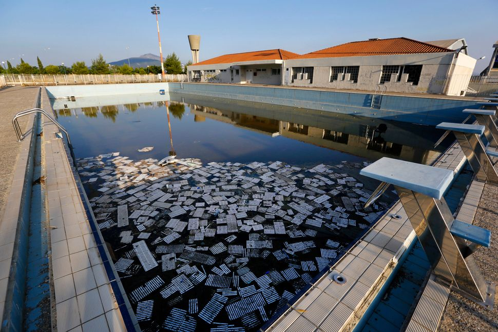 Garbage floats in a deserted swimming pool at the Olympic Village in Thrakomakedones, north of Athens, in July 2014.