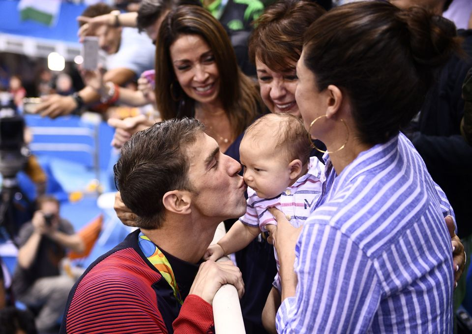 USA's Michael Phelps (L) kisses his son Boomer next to his partner Nicole Johnson (R) and mother Deborah (C) after he won the