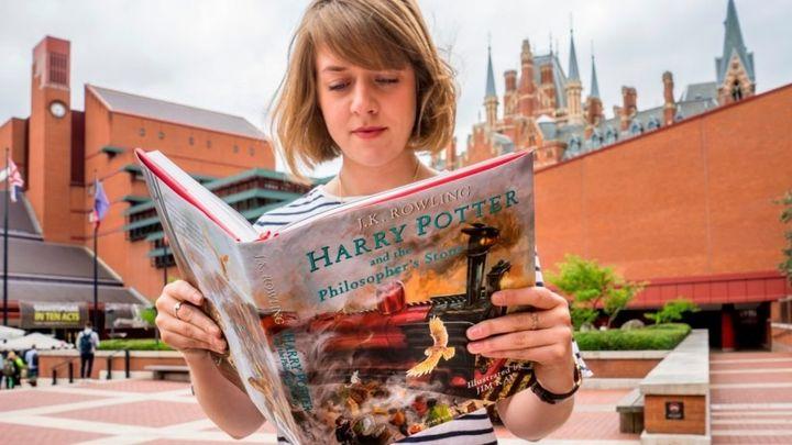 British Library employee reading <i>Harry Potter and the Philosopher's Stone</i>. Courtesy of photographer Tony Antoniou and
