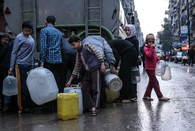 SYRIA. MARCH 5, 2016. Children fill containers with drinking water from a tanker in Salah al-Din, Aleppo....
