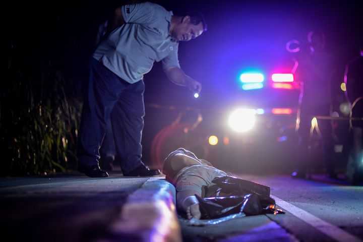 A member of the police's homicide division inspects the corpse of a suspected drug addict and victim of a vigilante-style exe