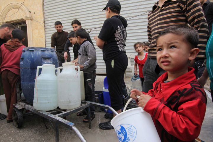 Residents and children wait to collect water in Aleppo, April 2, 2013. Around Syria, water shortages are worsening and suppli