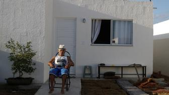 "Jose Gomes, 65, who has lived in the Vila Autodromo slum for 35 years, poses outside his new house which is one of the twenty houses built for the residents who refused to leave the community, in Rio de Janeiro, Brazil July 31, 2016. Picture taken July 31, 2016. REUTERS/Ricardo Moraes       SEARCH ""VILA AUTODROMO"" FOR THIS STORY. SEARCH ""THE WIDER IMAGE"" FOR ALL STORIES"