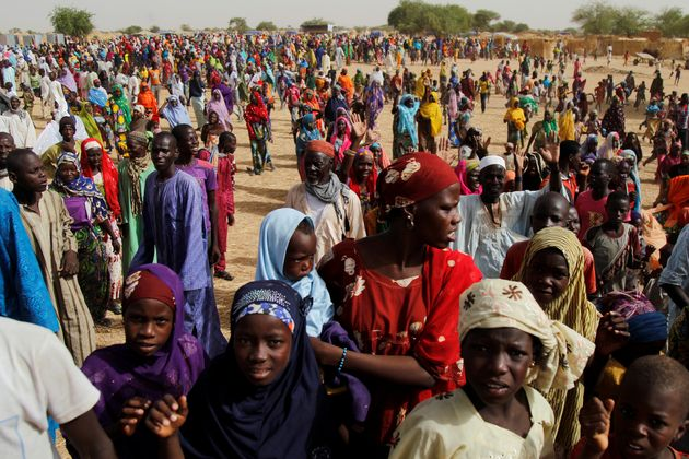 Nigerian refugees and displaced Nigeriens gather at a site for displaced persons in southeastern...