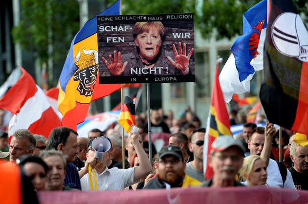 Demonstrators gather in front of a railway station under the banner 'We for Berlin - We for Germany'...